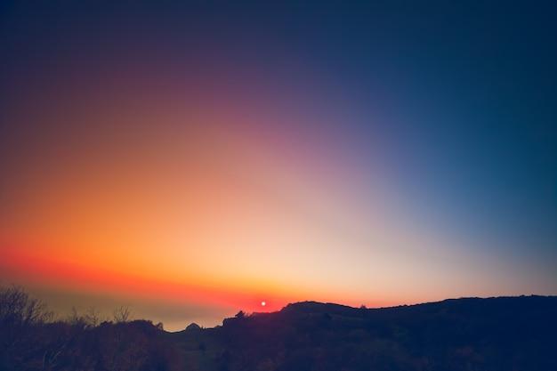 Mooie zomerse landschap in de bergen met de zon bij dageraad kleurrijke blauw oranje roze lucht