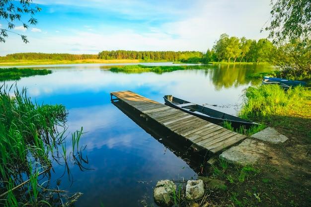Mooie zomerse landschap met pier en boot