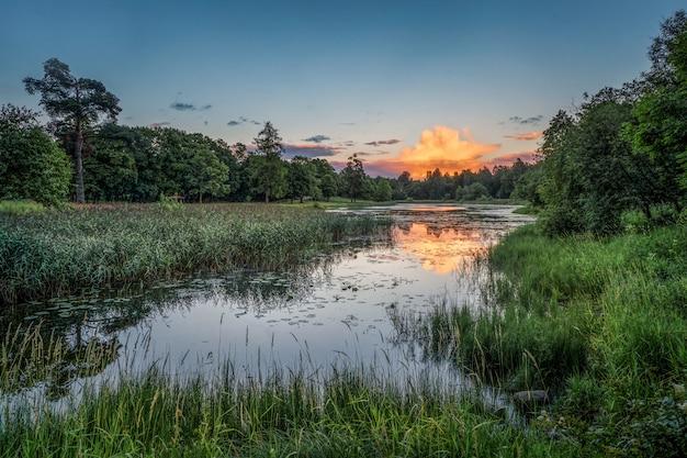 Mooie zomerse zonsondergang. roze wolkenbezinning over het meer.