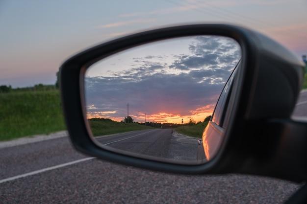 Mooie zomerse zonsondergang weerspiegeld in de zijspiegel van de auto. uitzicht vanuit het autoraam op de weg.