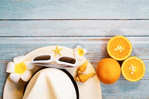 Mooie zomervakantie, strand accessoires, zonnebril, hoed, sinaasappels en schelpen op houten achtergronden