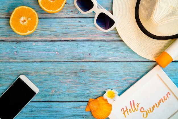 Mooie zomervakantie, strandaccessoires, oranje, zonnebril, hoed, sunblock en smartphone