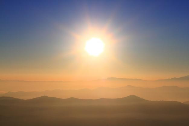Mooie zonsondergang en zonsopgang op hemel en gouden schemeringtijd met mist en mist in vallei van berglaag