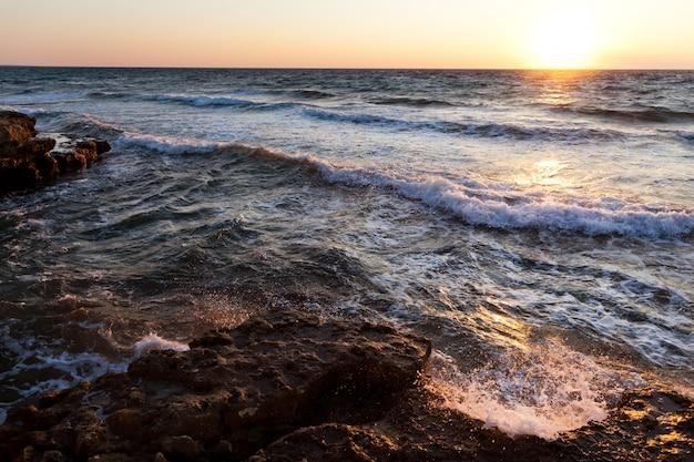 Mooie zonsondergang over golvende stormachtige rotsachtige kustlijn van de zwarte zee in de krim op de zomerdag