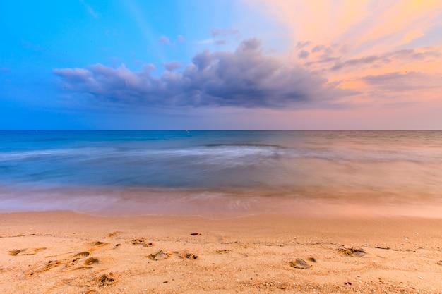 Mooie zonsonderganghemel en tropische strand en overzeese golf