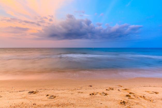 Mooie zonsonderganghemel over tropisch overzees en strand