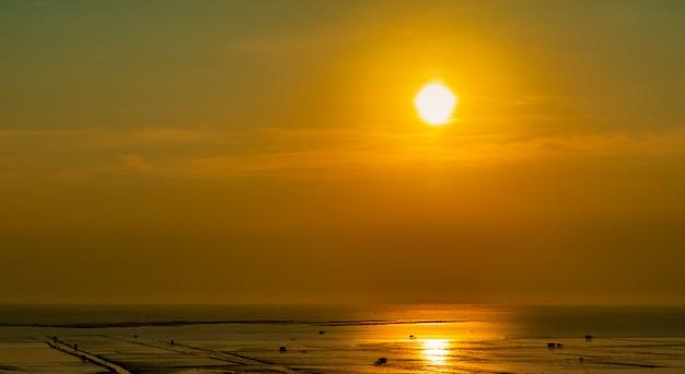 Mooie zonsonderganghemel. strand zonsondergang. twilight zee en lucht. tropische zee in de schemering. dramatische oranje en gouden hemel.