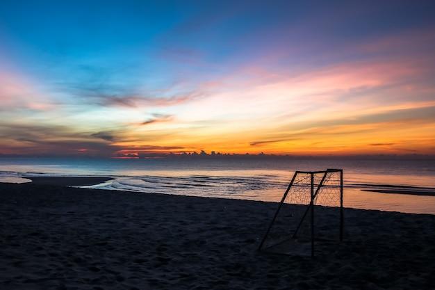 Mooie zonsondergangzonsopgang op het strand met klein silhouet