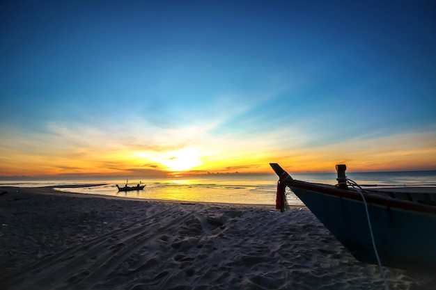 Mooie zonsondergangzonsopgang op het strand met silhouetboot