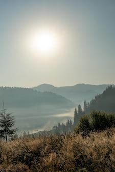 Mooie zonsopgang in bergen met witte mist onder panorama.