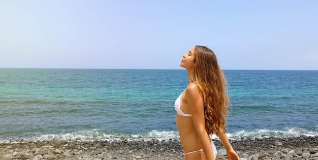 Mooie zorgeloze vrouw diep adem op het strand