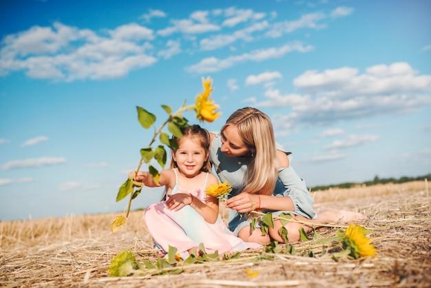 Mooie zorgzame moeder zit op het veld met haar mooie dochtertje