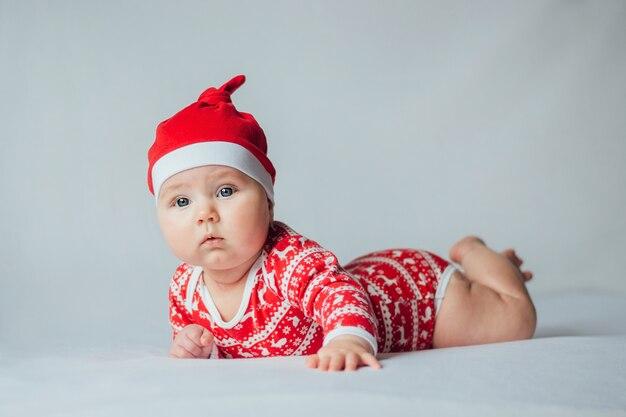 Mooie zuigelingsbaby in kerstmiskostuum op wit.