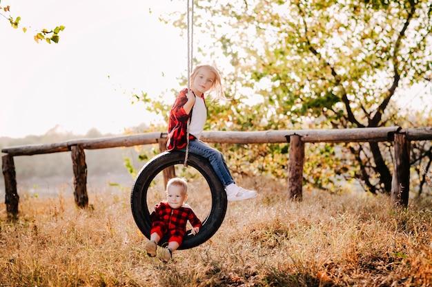 Mooie zus en broer in een rood geruit overhemd rijden een band aan een touw aan een boom in het park