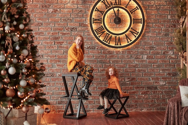 Mooie zussen die op kerstavond in een stijlvolle woonkamer zitten.