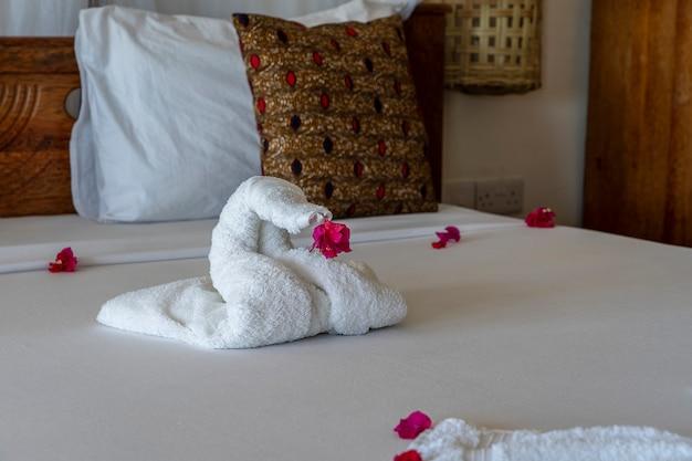 Mooie zwaan van witte badhanddoek versieren op bed