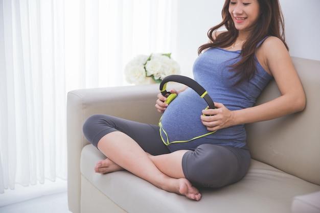 Mooie zwangere aziatische vrouw die hoofdtelefoon op haar babybuil gebruikt