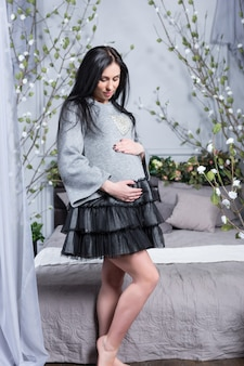 Mooie zwangere brunette vrouw in een jurk handen houden op buik staande in de buurt van bed met bloemen op het ledikant in de slaapkamer. laatste maanden zwangerschap.