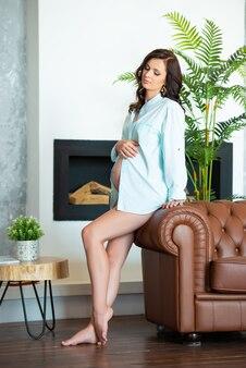 Mooie zwangere brunette vrouw in een mans shirt zit op een bank in een woonkamer.