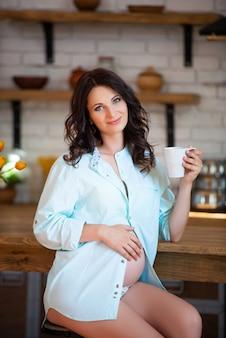 Mooie zwangere brunette vrouw in een shirt zit in de keuken met een kopje thee.
