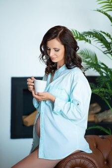 Mooie zwangere brunette vrouw in een shirt zit op een bank houdt een kopje vast en drinkt thee