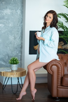 Mooie zwangere brunette vrouw in een shirt zit op een bank in een woonkamer