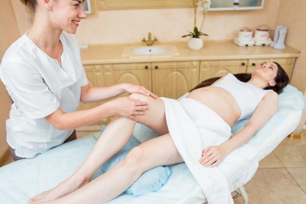 Mooie zwangere brunette vrouw met lang haar geniet van een snuifje massage van handen in een cosmetologie kamer