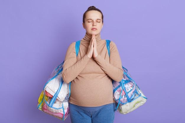 Mooie zwangere geconcentreerde vrouw in vrijetijdskleding met grote babybult