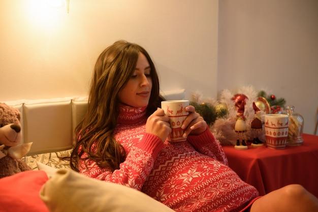 Mooie zwangere jonge vrouw op kerstmis, die een rust op kerstmisvakantie heeft. grote zwangere buik