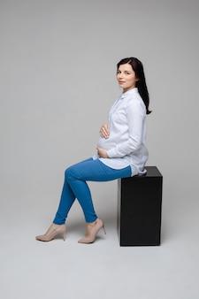 Mooie zwangere kantoormedewerker in hakken omarmen buik.