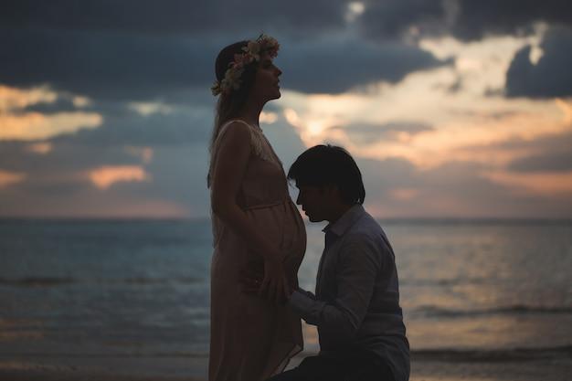 Mooie zwangere meisje en man bij zonsondergang