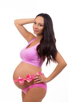 Mooie zwangere moeder verwacht baby met een roze strik op de buik.