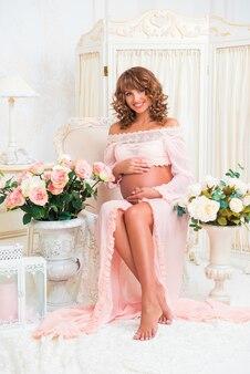 Mooie zwangere roodharige vrouw in tedere perzikjurk zit in de buurt van vazen met rozen