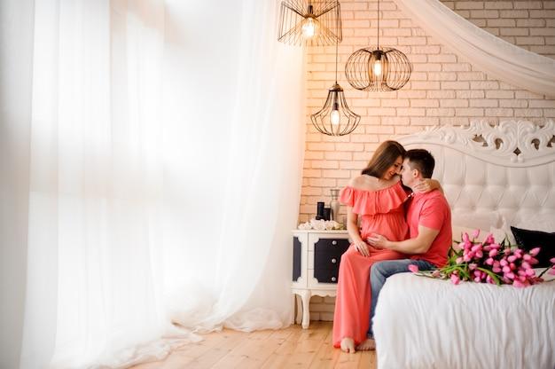 Mooie zwangere vrouw en haar echtgenoot die en op het witte bed zitten glimlachen
