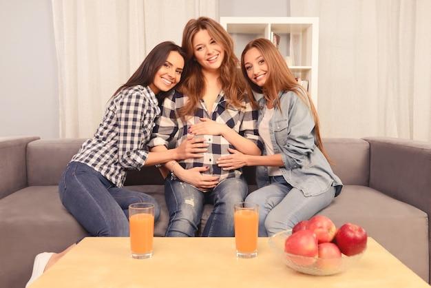 Mooie zwangere vrouw en haar gelukkige vriendinnen die op bank zitten
