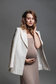 Mooie zwangere vrouw in beige jurk en wit jasje
