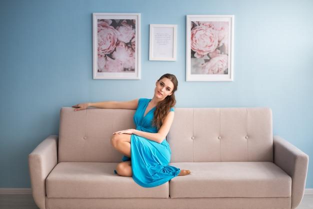 Mooie zwangere vrouw in een blauwe jurk zit op de bank.