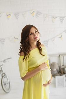 Mooie zwangere vrouw in een gele jurk in de studio