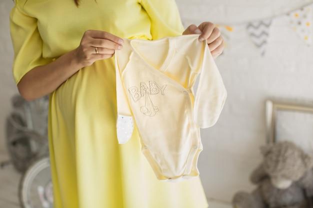 Mooie zwangere vrouw in een gele jurk in de studio.