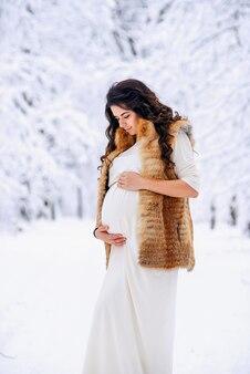 Mooie zwangere vrouw in een lange lichte jurk en jas houdt zachtjes haar buik met haar handen in een