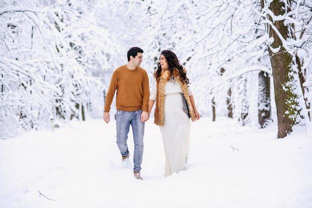 Mooie zwangere vrouw in een lange lichte jurk en jas met haar man in een trui en spijkerbroek