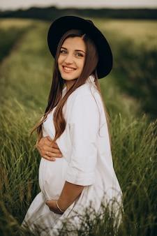 Mooie zwangere vrouw in een veld