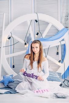 Mooie zwangere vrouw in een witte jurk zit tussen de stijlvolle kussens tegen de achtergrond van een groot wit wiel met gloeilampen en houten schermen en een zwangere buik
