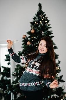 Mooie zwangere vrouw in gezellige kleding in de buurt van boom. vrolijk kerstfeest. kerst versierd interieur. zwangerschap, vakantie, mensen en verwachting concept. detailopname.