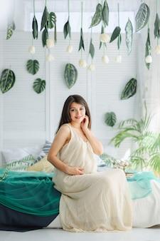 Mooie zwangere vrouw liggend op het bed met een groot boeket bloemen. zwangerschap concept