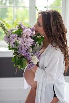 Mooie zwangere vrouw met een boeket van lila in haar handen in een moderne stijl badkamer