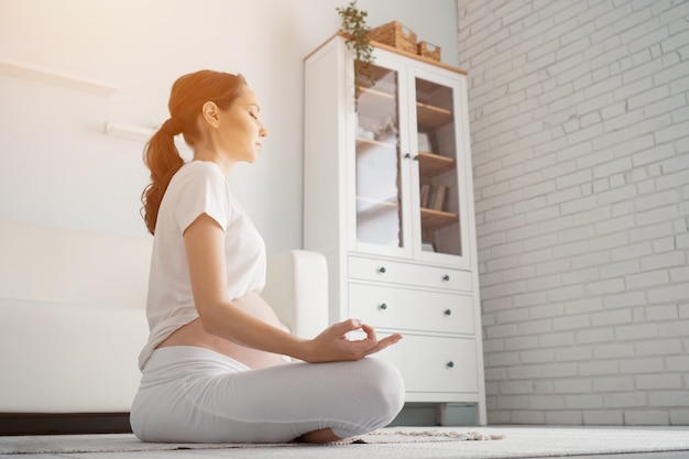 Mooie zwangere vrouw met grote blote buik mediteert thuis in lotushouding