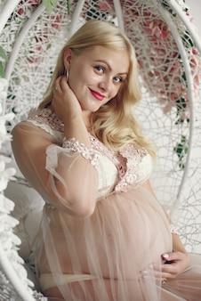 Mooie zwangere vrouw met grote buik in een studio