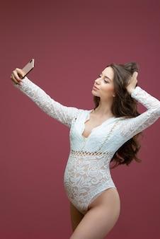 Mooie zwangere vrouw met lang haar gekleed in witte kanten lingerie met een pak doet een selfie op een roze achtergrond in de studio.