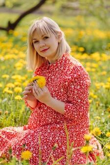 Mooie zwangere vrouw ontspannen in het park, gekleed in rode jurk